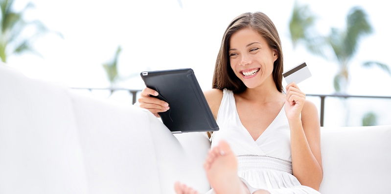 Woman shopping on tablet computer and credit card sitting in sof