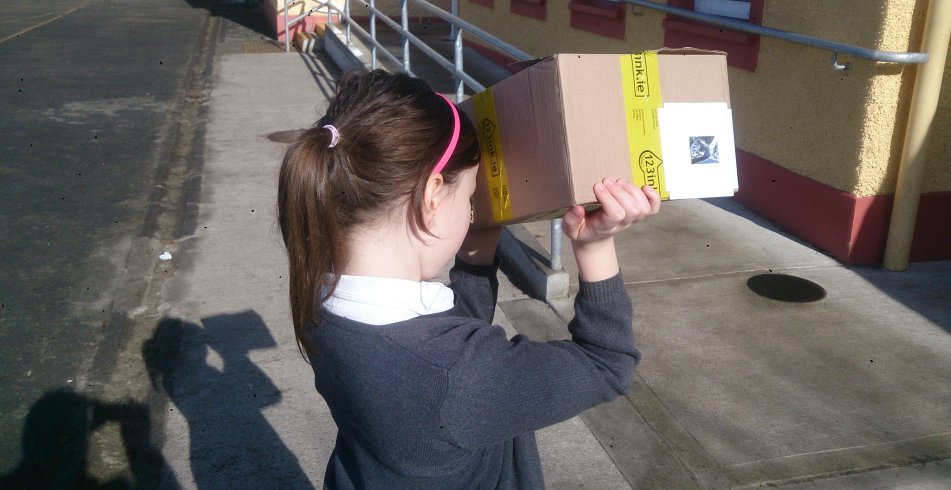 Méadhbh Ní Mhuíneachain, a pupil at Ballynacally NS in County Clare, views the solar eclipse using a pinhole camera